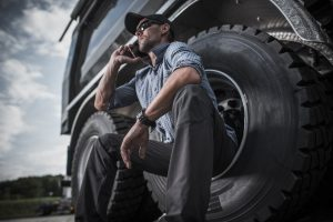 truck-driver-sitting-against-wheel-while-talking-on-cell-phone