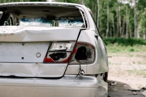 damaged car viewed from behind after a semi truck rear ended it