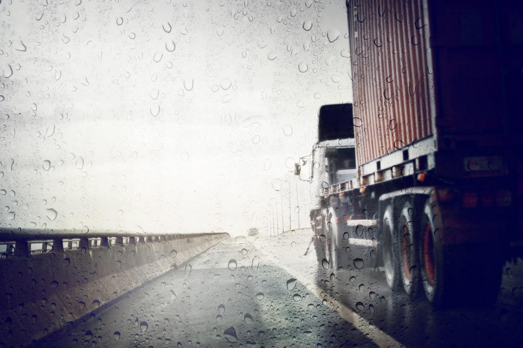 A semi truck driving too fast for the weather conditions on a highway during a rain shower