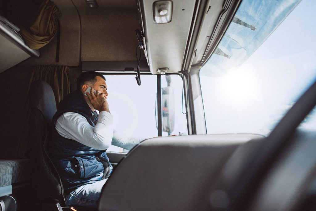 a distracted truck driver talking on his cell phone behind the wheel of his semi truck