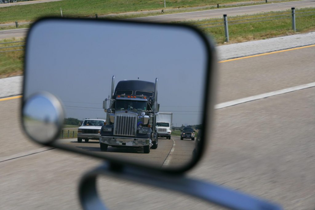 a semi truck following too close as viewed from a rear view mirror