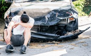 a sad man sits in front of his car after being run off the road by a semi truck