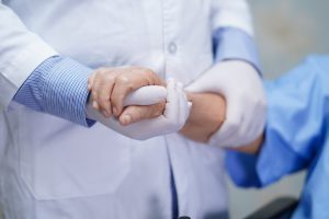 A doctor wearing rubber gloves holds a patient's hand and forearm.