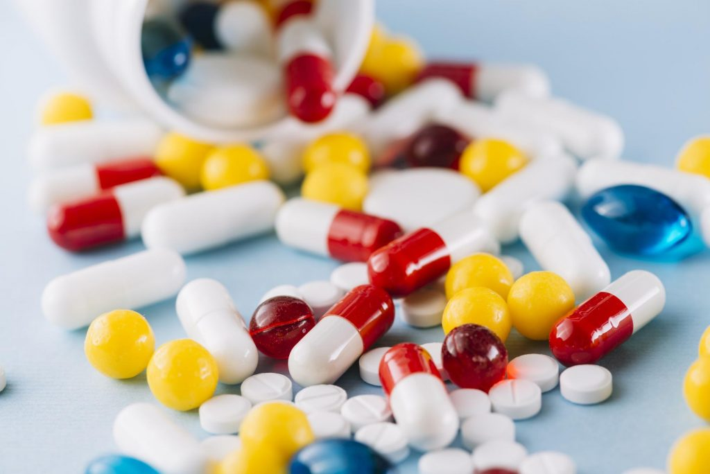 A mixture of pills and medication capsules of different shapes and colors is poured out of a prescription bottle. In correct dosages or prescriptions can amount to medical malpractice.