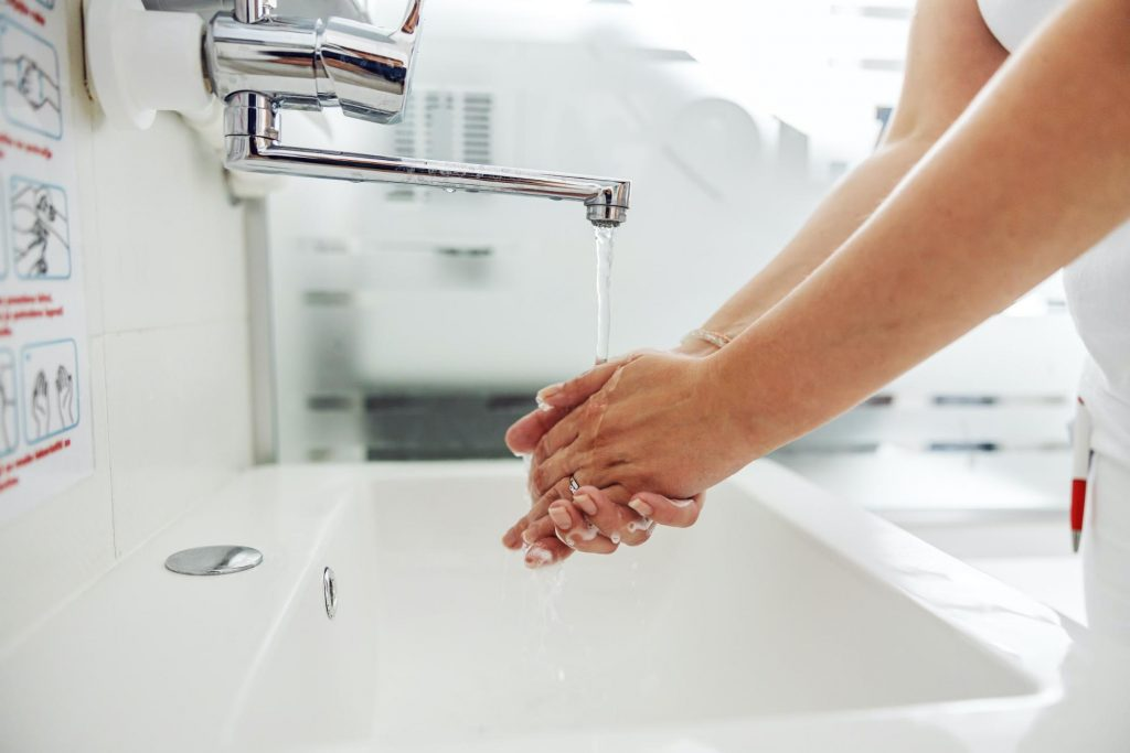 A nursing home staff member washes their hands in a sink. Poor hygiene by staff members is a nursing home red flag.