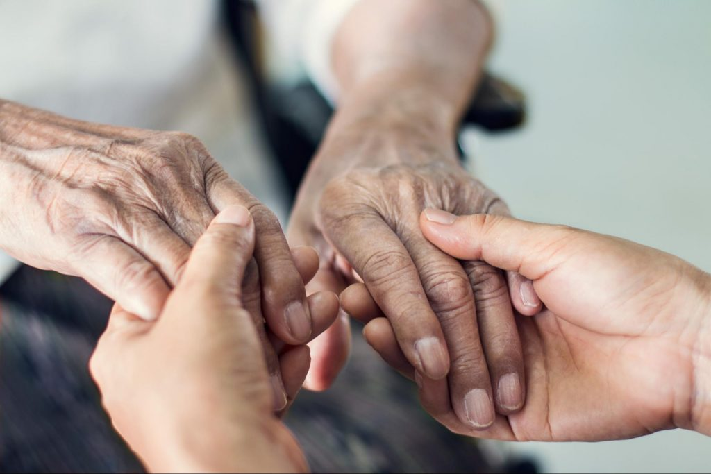 A young person holds an older persons hands in a nursing home as they look for signs of nursing home red flags or abuse.