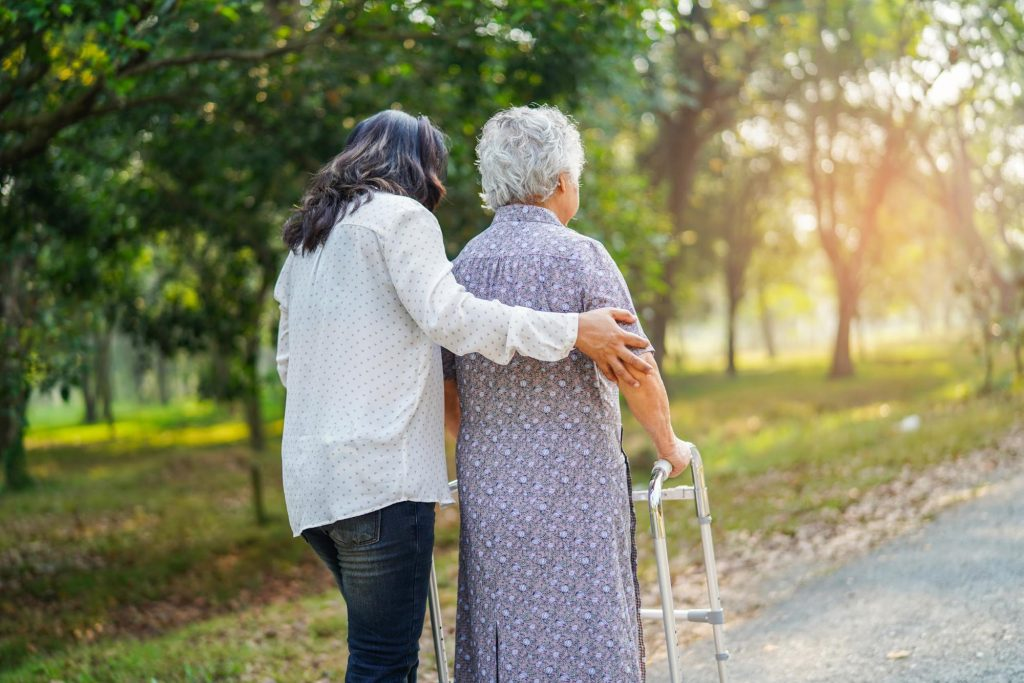 A nursing home staff member takes a resident for a walk outside. One red flag for nursing home abuse is when residents are not allowed to have outdoor activities.