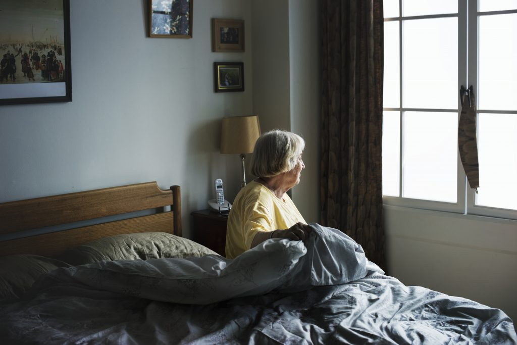 A senior woman sits alone in her room at a nursing home. A big red flag for nursing homes is when residents are isolated and family members are not allowed to visit them.