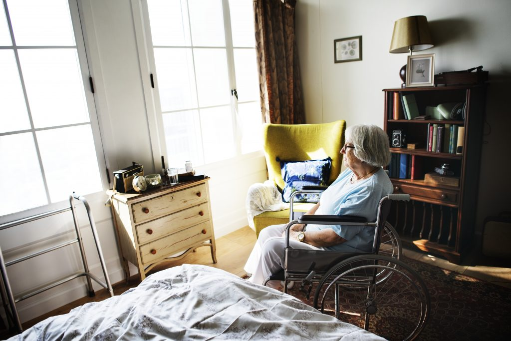 Senior woman sitting alone in her bedroom at a nursing home in the middle of the afternoon.