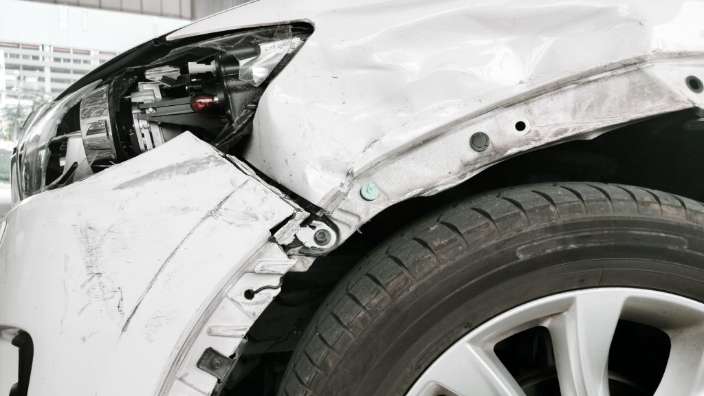 Close up photo of a car with a damaged front fender and bumper from a car accident. Drivers who have been in a car accident should speak with an attorney to guide them through the sometimes confusing auto accident laws that apply to their case.