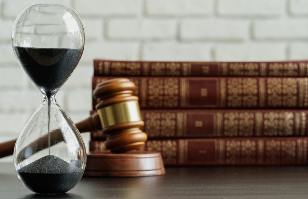 An hourglass sits on a table in front of a judges gavel and a stack of legal books. After a car accident in Kentucky, victims have a limited amount of time to file a claim for compensation.