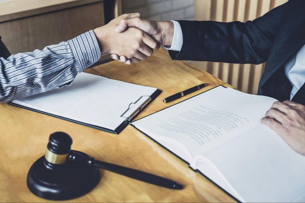An attorney and client shake hands over a desk with a decorative gavel in the foreground at the end of a slip and fall case. It can take a months or years to settle a slip and fall claim but it is important to remain patient during negotiations.