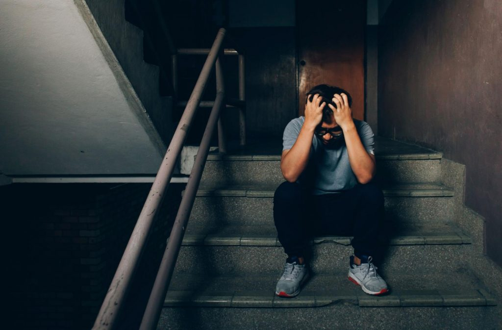 A depressed man sits on a dark stairway holding his head in his hands. An injury from a slip and fall accident can leave both physical and emotional injuries.