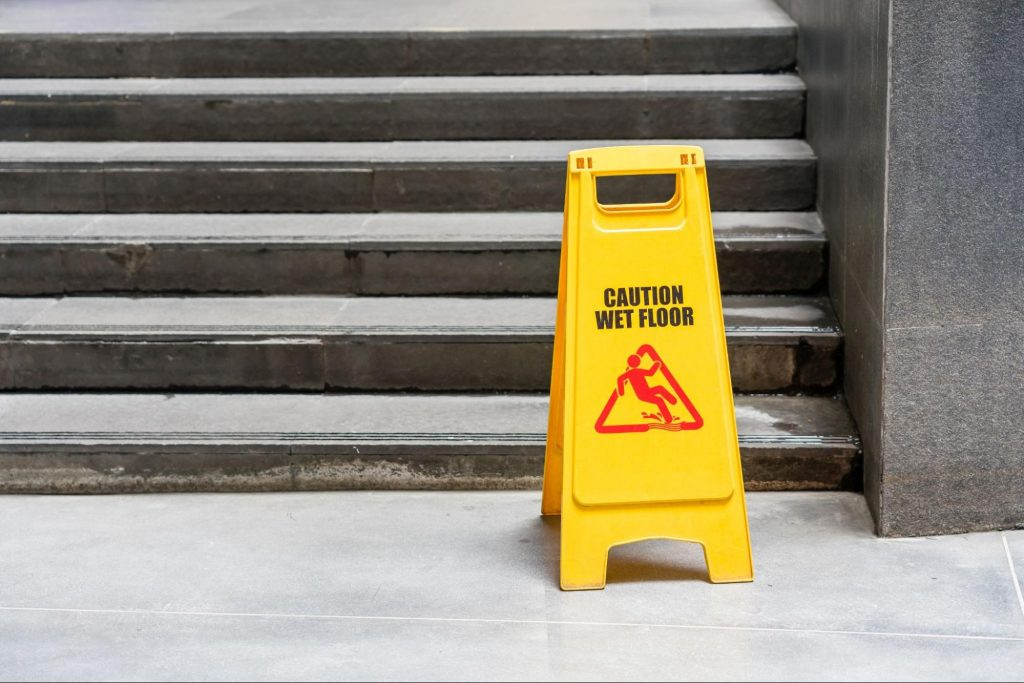A wet floor caution sign in front of a set of stairs. Uneven pavement and staircases are common slip and fall hazards.