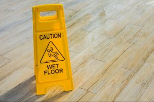 A wet floor caution sign on a recently mopped wooden floor. People who slip and fall in public places can seriously injure themselves which is why many property owners use these signs.