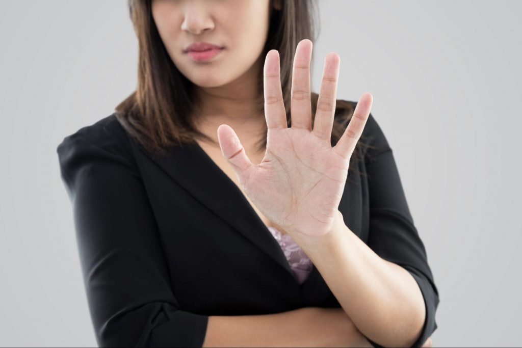 A woman holding her hand out to the camera to make a no gesture. The plaintiff in a slip and fall lawsuit has the right to refuse settlement offers and renegotiate for a better offer.