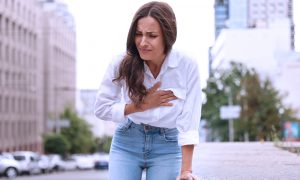 Woman with chest pain clutching chest