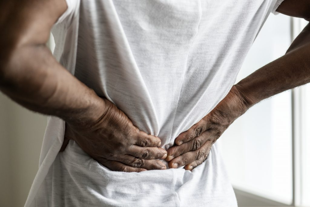 Man holding hands to lower back to soothe pain.