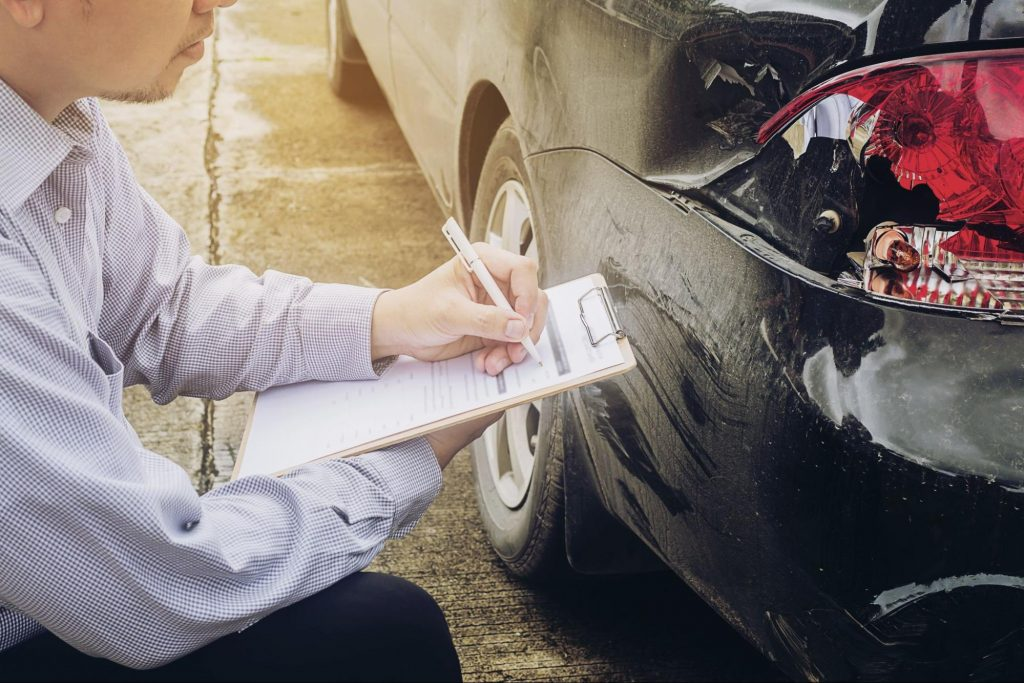 Insurance adjuster inspecting a car after and accident.