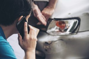 Insurance agent working during on site car accident claim process - people and car insurance claim concept