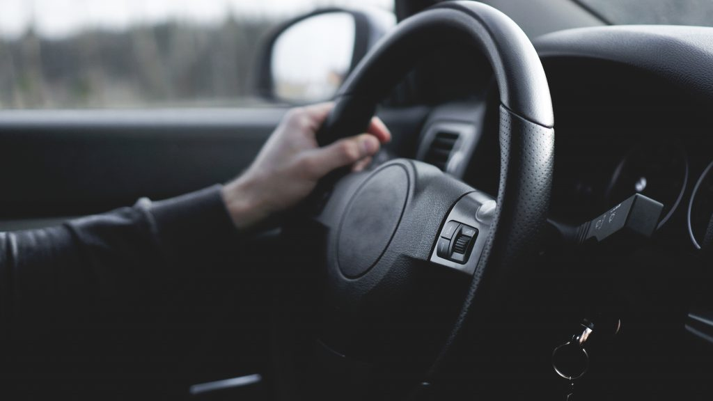 A woman's hand on the steering wheel of her car.