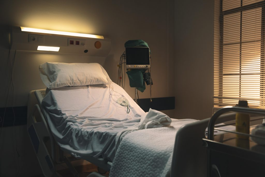 Empty hospital bed in hospital room.