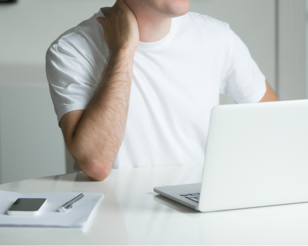 man holding neck in pain sitting at computer.